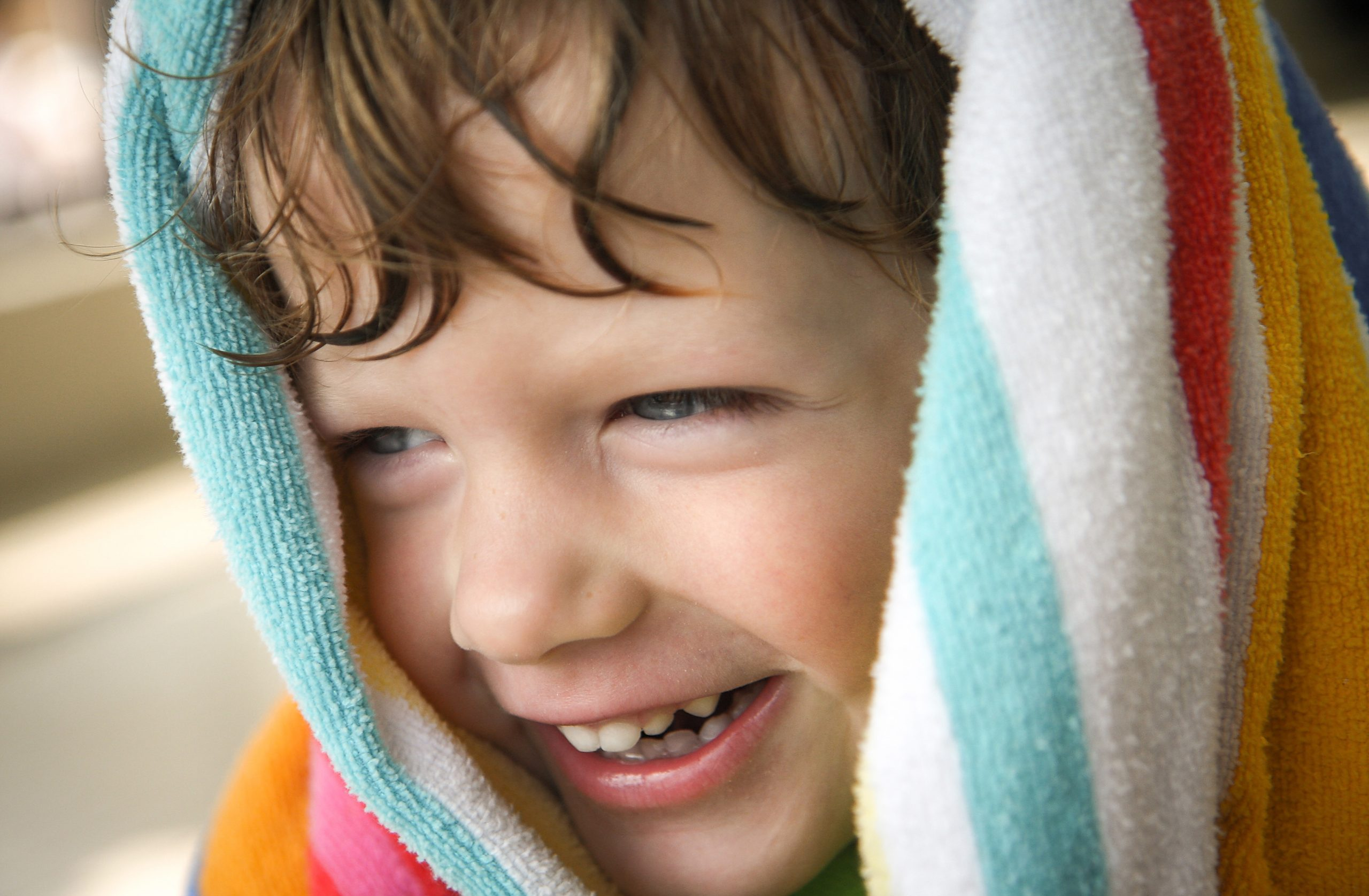 A young boy with a towel wrapped around his head smiles while drying off after getting out of a pool.