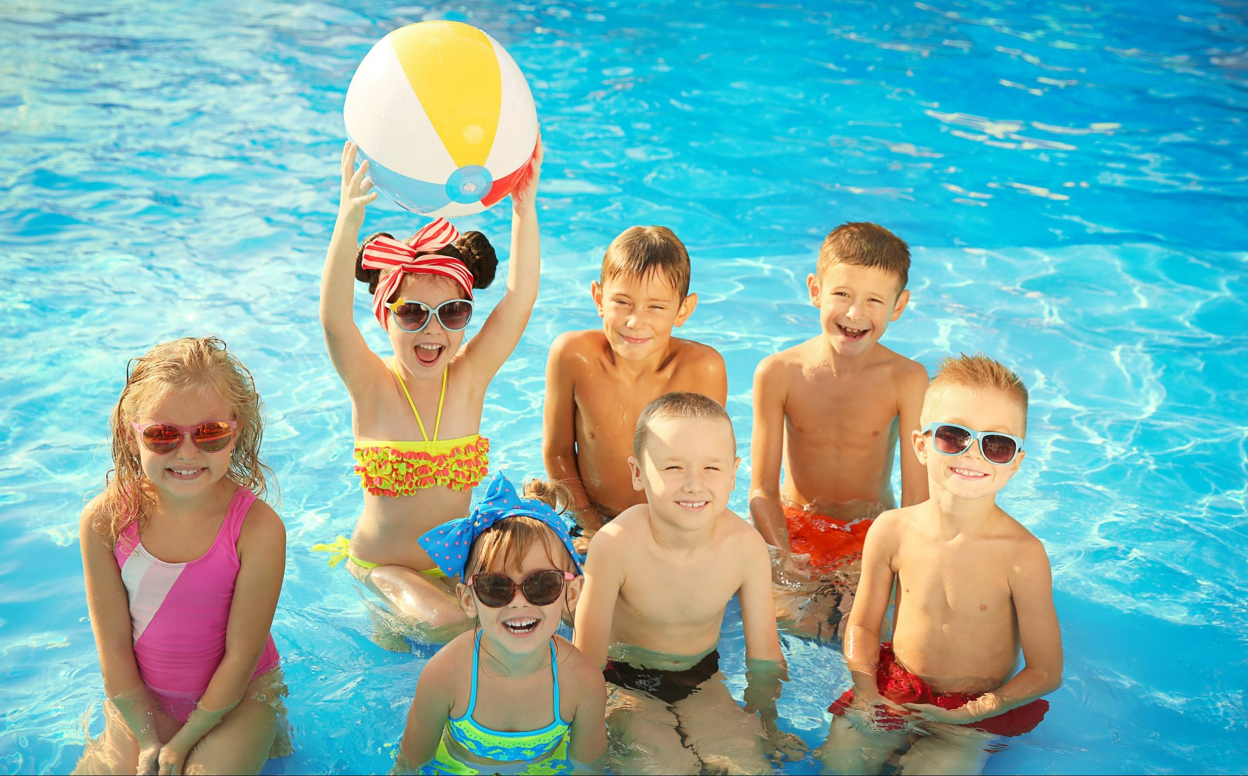 Little kids at swimming pool on sunny day
