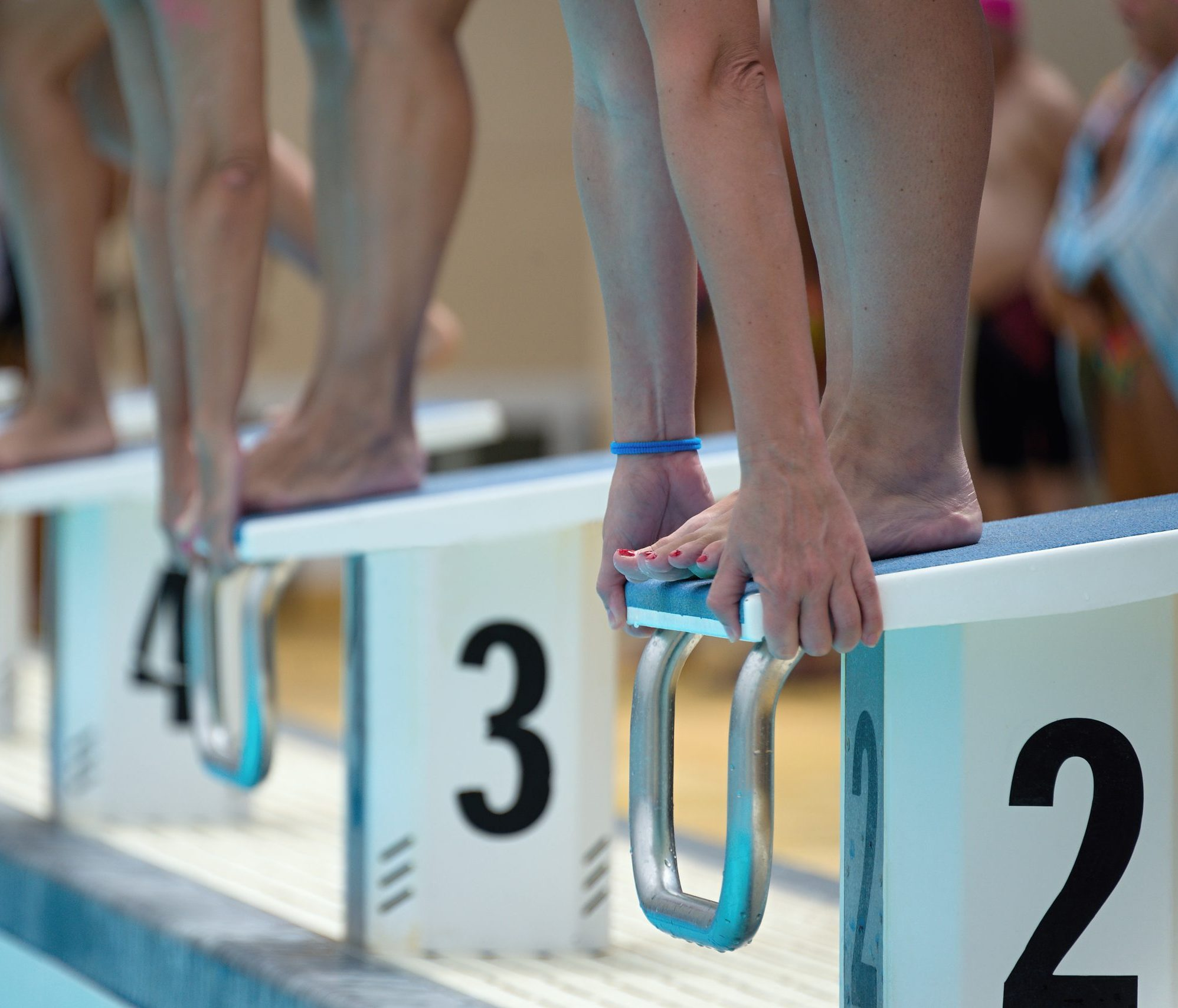 Swimmers on the starting blocks at the beginning of a race