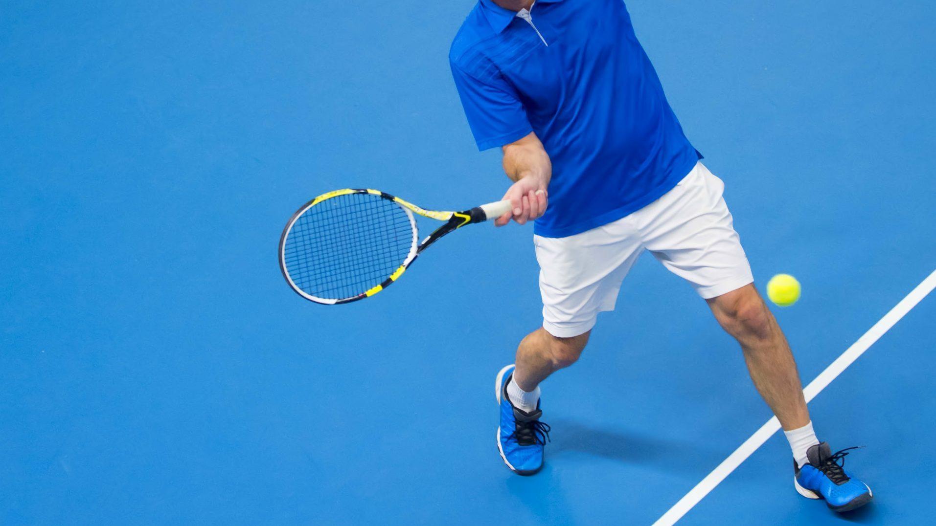 man playing tennis on blue floor